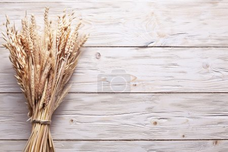 Photo for Ears of wheat on old wooden table. - Royalty Free Image