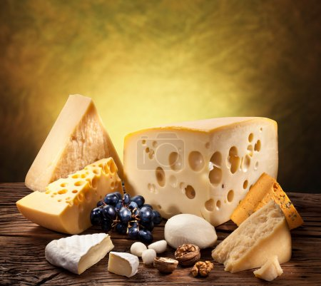 Photo for Different types of cheese over old wooden table. - Royalty Free Image