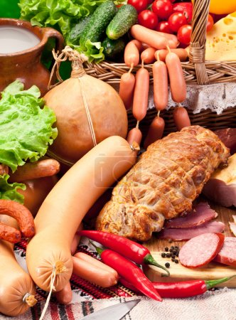 Variety of sausages with vegetables and milk products.