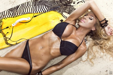 Attractive girl with a yellow kite board on the be...