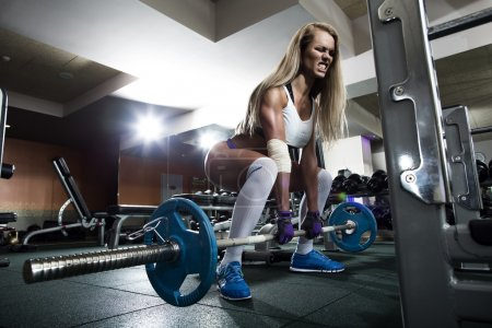 Photo for Sportive woman lifting weights in training gym - Royalty Free Image