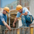 Two authentic construction workers collaborating i...