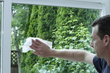 man cleaning a sliding glass door