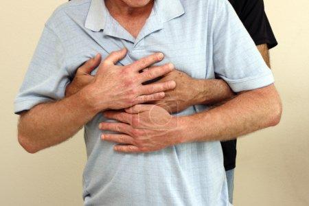 Photo pour Homme derrière un autre homme tenant l'homme à l'avant avec les bras et les mains enroulées autour de sa poitrine. l'homme en face a ses mains sur le dessus de l'homme qui lui tient. - image libre de droit