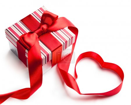 Foto de Caja de regalo de vacaciones con cinta roja en la forma de un corazón aislado sobre fondo blanco - Imagen libre de derechos