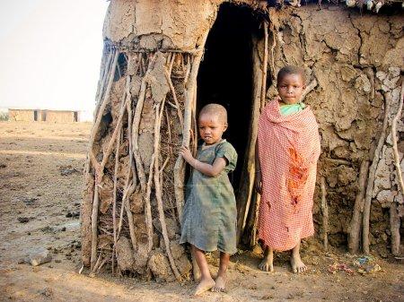 Photo pour KENYA, MASAI MARA - 6 JANVIER : Petits enfants debout à la porte de la maison de village de la tribu Masai, le 6 janvier 2004 à Masai Mara, Kenya. Problème social des pays africains pauvres . - image libre de droit