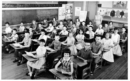Photo pour Une photo de 1959 d'une salle de classe avec des enfants assis à des bureaux et professeur debout à l'arrière de la salle . - image libre de droit