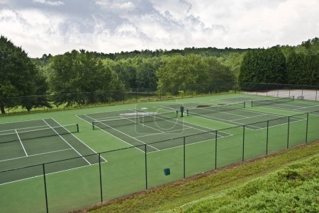 Photo for Tennis courts that have been abandoned because of rainy weather, there are puddles of water on some - Royalty Free Image