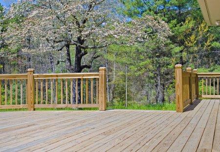 Photo pour Une nouvelle terrasse en bois sur le côté d'une maison avec cornouiller en fleurs . - image libre de droit