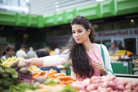 Photo pour Jolie jeune femme, acheter des légumes sur le marché - image libre de droit