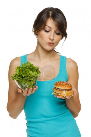 woman making decision between healthy salad and fast food
