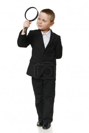Full length of a schoolboy in black suit looking through the magnifying glass