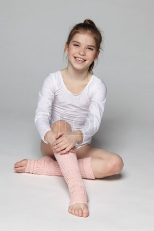 little girl wearing sport clothing sitting on the floor