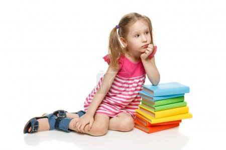 little girl sitting on the floor leaning on the stack of books