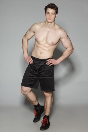 Athletic young man shirtless standing in full length