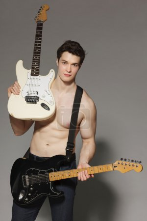 Young muscular man with bare torso handing two electric guitars