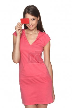 Smiling female wearing sport style pink dress showing blank credit card