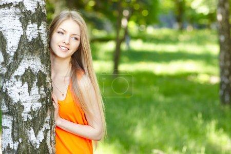 Beautiful female peeping from behind tree