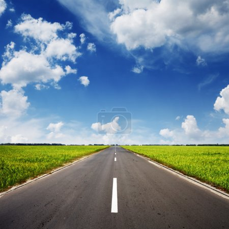 Photo for Asphalt road through the green field and clouds on blue sky in summer day - Royalty Free Image