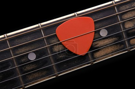 Photo for Orange guitar pick on the fingerboard - Royalty Free Image