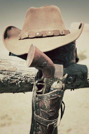 Photo pour Pistolet de cow-boy et chapeau en plein air dans un ranch - image libre de droit
