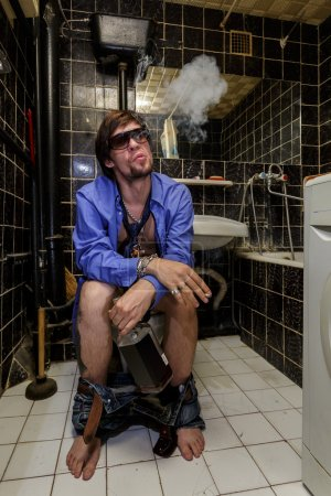 Drunk Man sits in a toilet with a bottle of whiskey and smoking