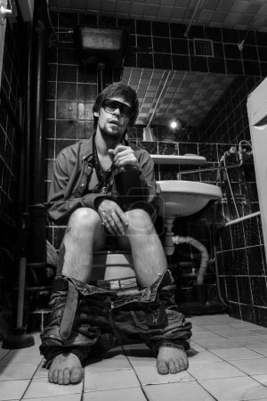 Drunk Man sits in a toilet with a bottle of whiskey