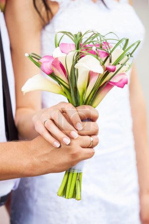 Closeup view of a bride and groom's hands with bouquet of callas