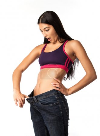 Astonished young woman in old jeans pant after losing weight