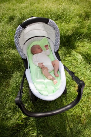 Baby boy sleeping in the pram outdoors, view from above