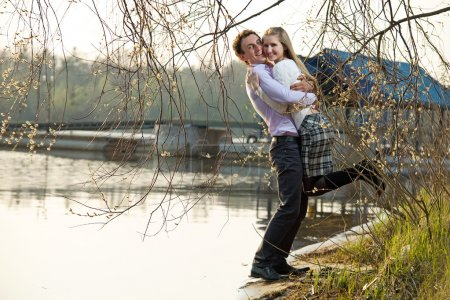 Photo for Young couple having fun on river beach in early spring - Royalty Free Image