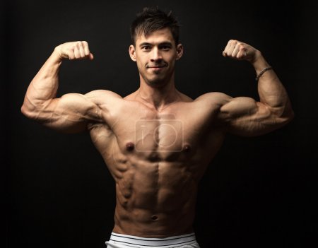 Photo for Waist-up portrait of muscular man flexing his biceps against black background - Royalty Free Image