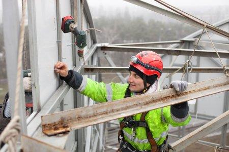 Foto de Escalador industrial en la parte superior de una construcción metálica - Imagen libre de derechos
