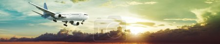 Photo for Jet plane is maneuvering for landing in a spectacular sunset sky. Panoramic composition. - Royalty Free Image