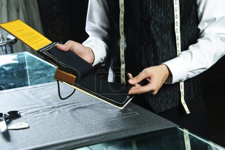 Tailor choosing suit textile from list of samples