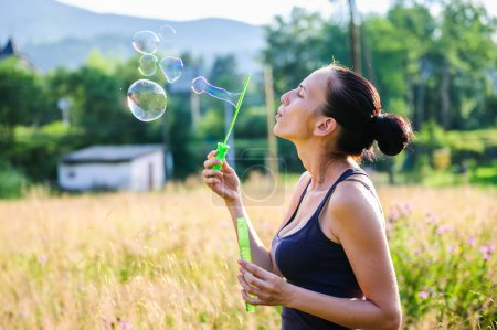 Yang and beautiful Slav woman plays with soap bubbled among summer field