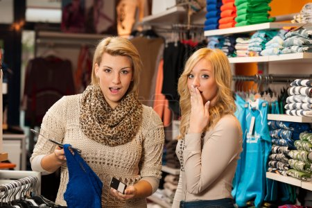 Two girls shocked by a price of clothes in a shop