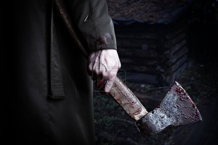 Axe with blood in male hand