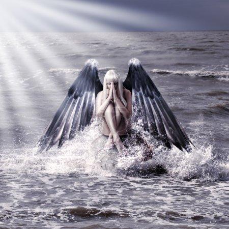 Photo pour Portrait de fantaisie de femme avec des ailes d'ange noir prier en étant assis en aérosol de mer pendant la tempête - image libre de droit