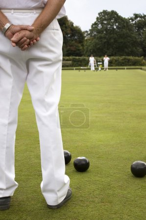 Photo for People dressed in white playing bowls on a bowling green. - Royalty Free Image