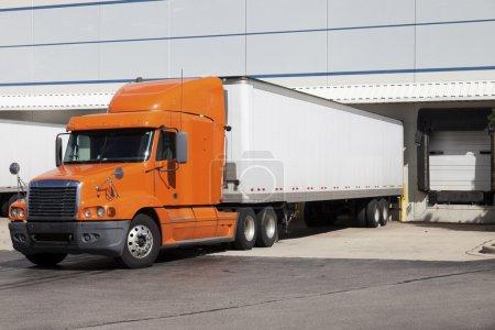 Photo pour Camion semi orange près de la porte de l'entrepôt - image libre de droit