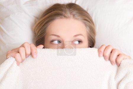 Photo pour Portrait de drôle belle jeune femme couché dans son lit sous couverture - image libre de droit