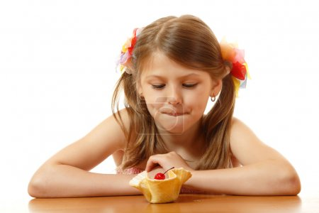 Little girl looking with appetite for delicious cake