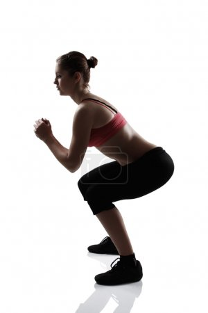 Sport girl doing squatting exercise