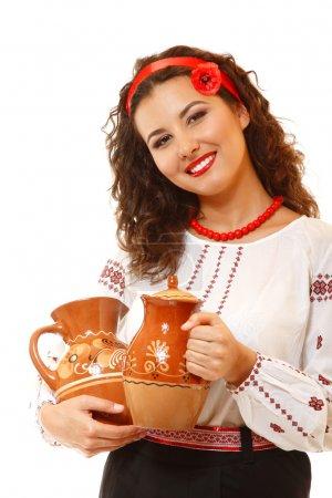 Photo pour Belle jeune femme ukrainienne dans native costume tenant des pots de terre cuite - image libre de droit