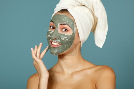 Photo for Spa teen girl applying facial clay mask. Over blue background - Royalty Free Image
