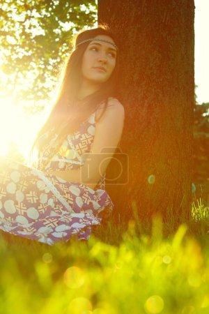 Photo pour Portrait en plein air de belle jeune fille assise sur l'herbe sous l'arbre - image libre de droit