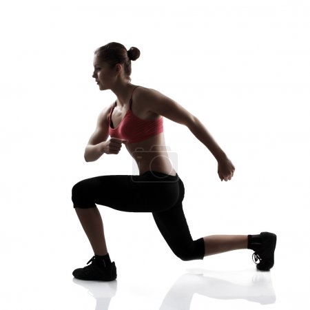Athletic woman doing lunge