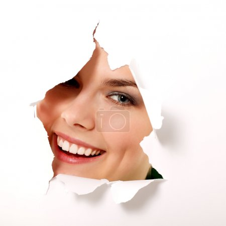 Girl peeping surprised through hole in paper