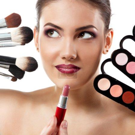 Photo pour Belle jeune femme avec des pinceaux de maquillage, rouge à lèvres et palette d'ombres à paupières - image libre de droit